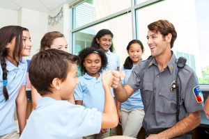 officer fist bumps student