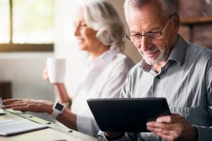 older man and woman using tablet