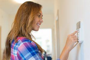 Young woman setting burglar alarm at home.