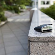 Wallet with cash inside sitting on a stone hand rail