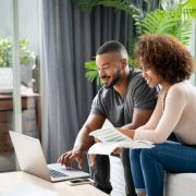 Loving couple paying bills online at home using a laptop computer and looking very happy - lifestyle concepts