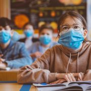 High school students at school, wearing N95 Face masks. Teenage girl wearing eyeglasses sitting at the school desk and listening to the teacher.