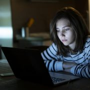 Young girl is reading alone on her laptop late at night