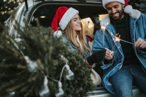 Happy couple is wearing Santa Claus hat and sitting in car trunk while enjoying their beautiful moments of Christmas tree adventure. It is a cold and sunny day outside.