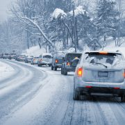 A line of cars slowly driving on a snowy, icy road. Entire image is monochrome blue-ish except the taillights, which are glowing red and yellow.