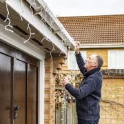 Senior man putting up or taking down outdoor Christmas lights from the gutter of a suburban house