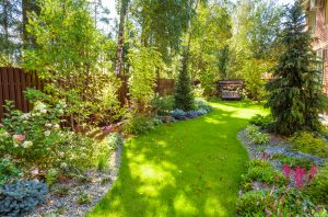 Landscape design with plants and flowers at residential house. Scenic view of nice landscaped garden in backyard.