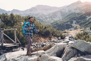 Backpacker crossing a stream in the mountains