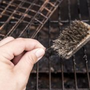 Person's hand showing loose bristle from wire grill cleaning brush. Dangerous when it sticks to meat or other food and a person accidentally swallows it. Digestion damage, life threatening situation.