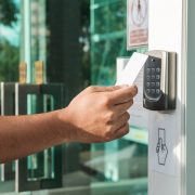 Hand using security key card scanning to open the door to entering private building. Home and building security system.