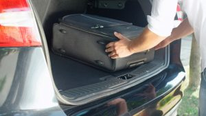 Person putting travel bags in a car trunk