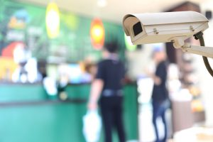 Security camera on blurred background of people in the cafe, concept of security and safety