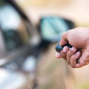 Image of someone using a car remote / keyless entry to unlock a car