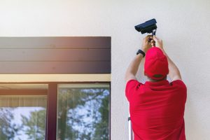 Professional technician installing home security camera, related to the topic of professional vs DIY security camera installation
